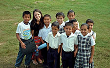 A UNF student in Belize poses with her class