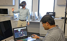 Dr. Sandeep Reddivari, seated, looks at a computer image of what student Jason Smith sees in virtual reality googles
