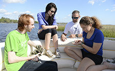 Students on a boat looking at a crab in UNF wetlands