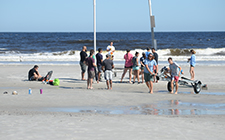 Students test components of a research project at the beach.