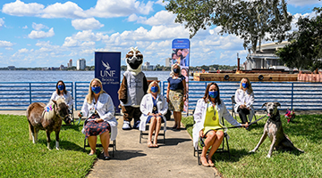 Group photo featuring the graduating practitioners, UNF's mascot Ozzie the Osprey, Dr. Carlene Taylor, UNF professor of the ADAPT program, and the ADAPT program's animal partners, Gypsy, an American Miniature Horse, and Asher, a Great Dane.