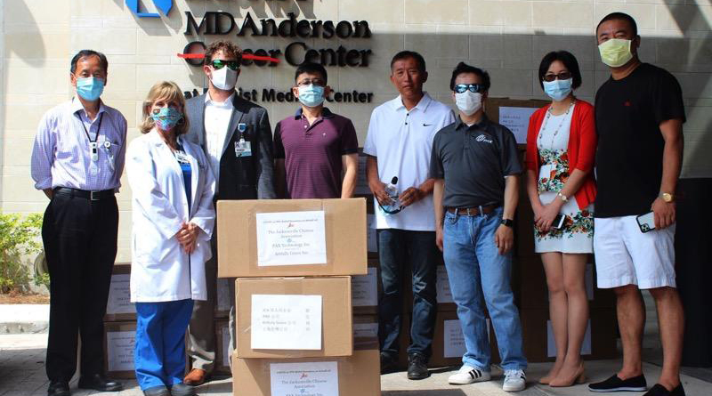 Group of Chinese community members standing with boxes of donated PPE supplies