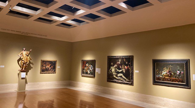 Snapshot of the inside of the Cummer museum featuring 4 still life portraits and a gold bust.