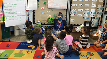 UNF preschool educator teaching students in a classroom. Everyone is wearing face masks while sitting on the floor.