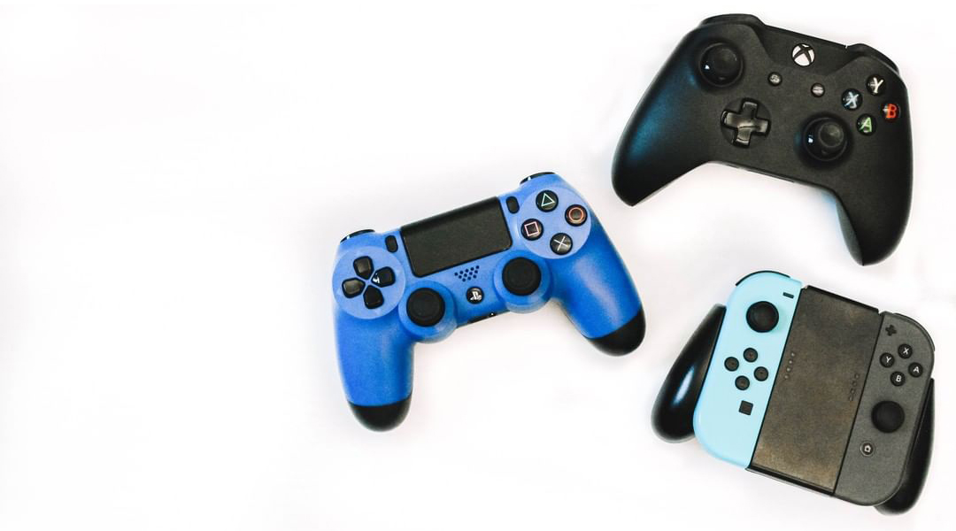 A PlayStation 4, Xbox One, and Nintendo Switch controller on a white background
