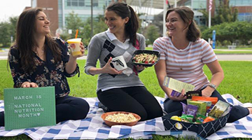 UNF dietitians sitting on a picnic blanket eating healthy snacks