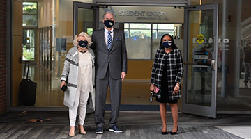 UNF President and First Lady Szymanski and Interim Provost Dr. Karen Patterson standing outside the Student Union wearing masks.