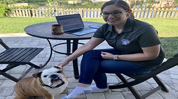 Maria Atilano at home on her porch with her bulldog