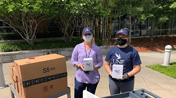 UNF volunteers holding boxes of blood pressure cuffs outside the Student Union building