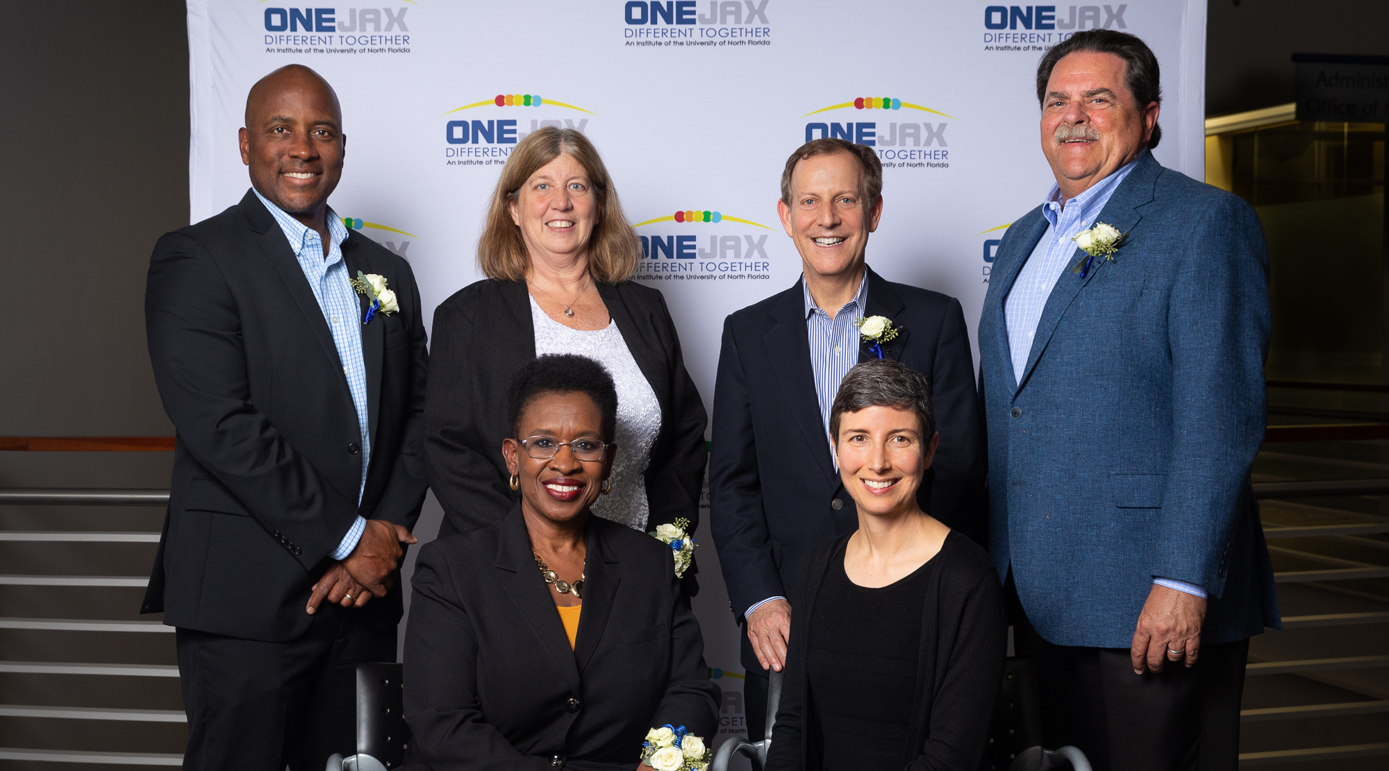 OneJax Humanitarian Award Honorees standing together against a OneJax backdrop