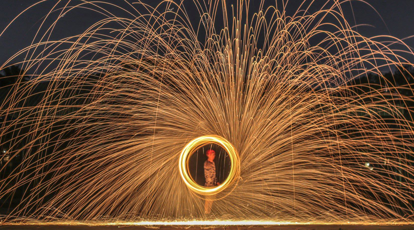 Lighting steel wool on fire and swinging it in circles to create an elaborate display of light