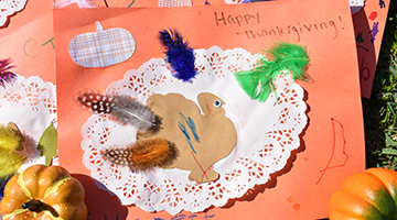 Thanksgiving-themed placemat featuring a cutout of a turkey, green feathers, glitter, and more