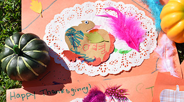 Thanksgiving-themed placemat featuring a cutout of a turkey, pink feathers, glitter, and more