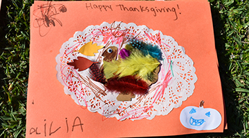 Thanksgiving-themed placemat featuring a cutout of a turkey, yellow feathers, glitter, and more