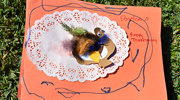 Thanksgiving-themed placemat featuring a cutout of a turkey, brown feathers, glitter, and more