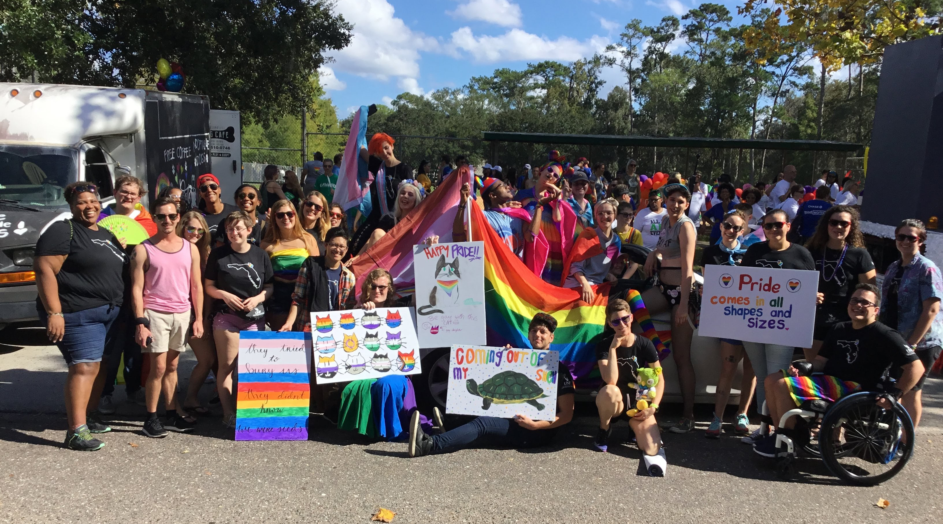 UNF students posing with flags and posters at a pride celebration