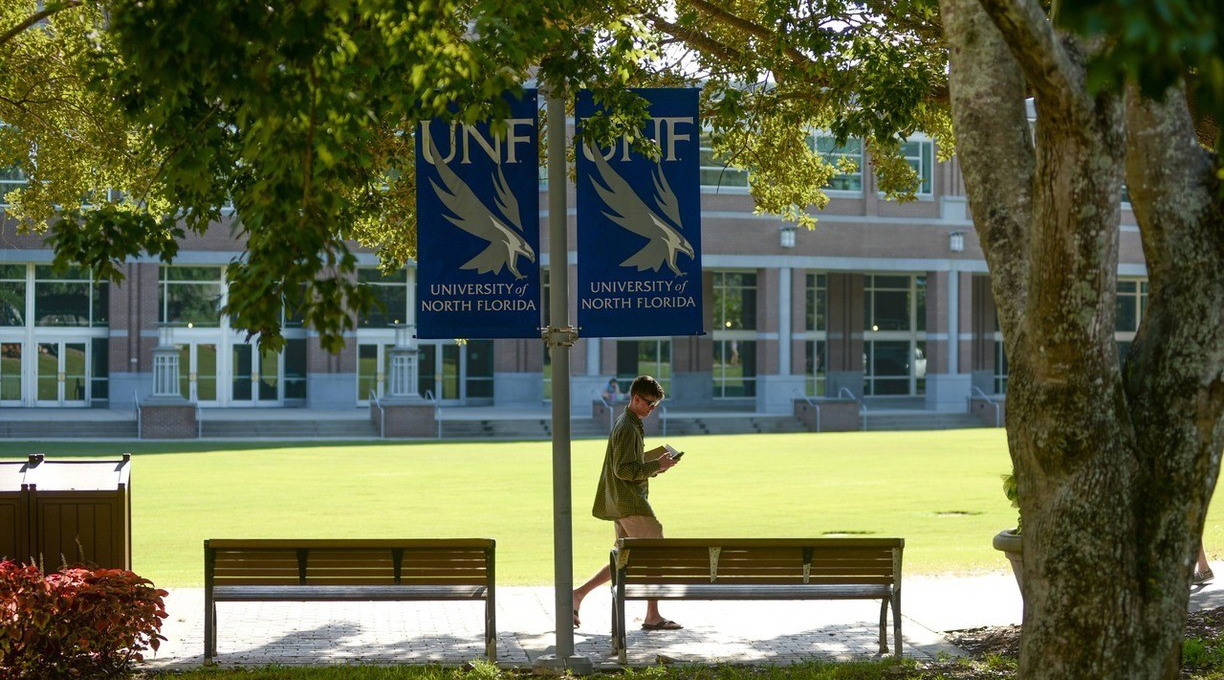 Student walking through the green on campus with UNF banners