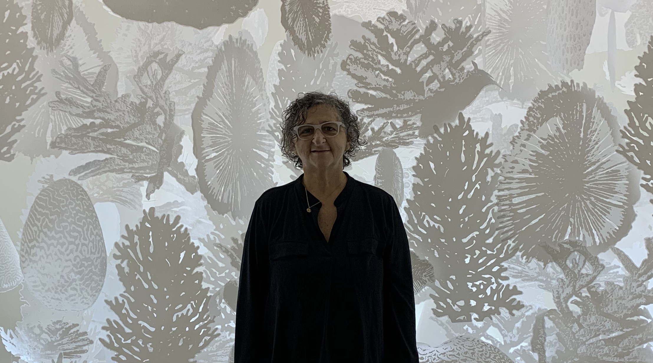 Sheila Goloborotko standing against a patterned gray background
