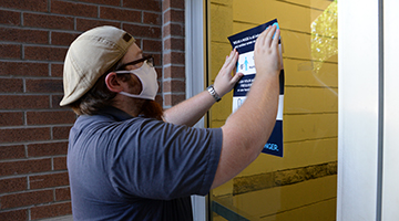 Employee installs vinyl safety sign on campus door