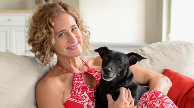 Dr. Jennifer Wesely and her dog sitting on a beige couch at home