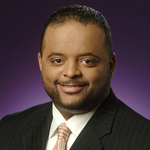 Headshot of Roland S. Martin on a purple background