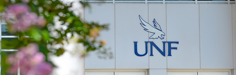 UNF logo sign with pink flowers blurred in the foreground