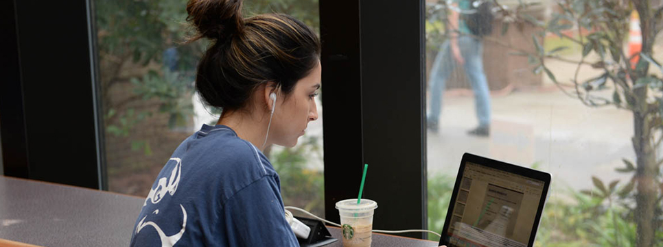UNF student sitting in campus coffee shop surfing her computer