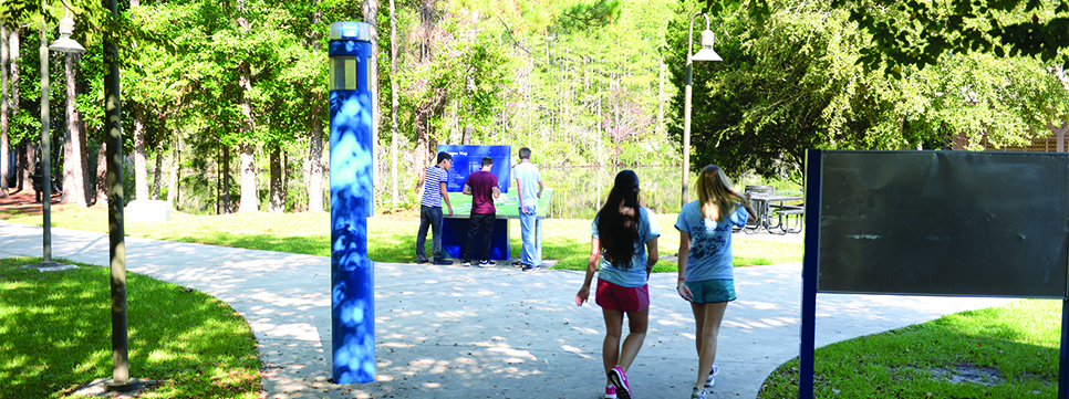 Students walking on campus and checking out the campus map.