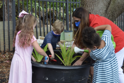 teacher planting plants with students outside
