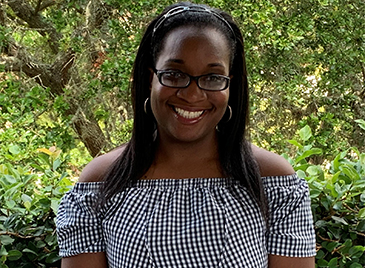 Danyelle smiling with glasses and a checkered top in front of green plants