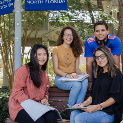 international students sitting on a bench and smiling at the camera