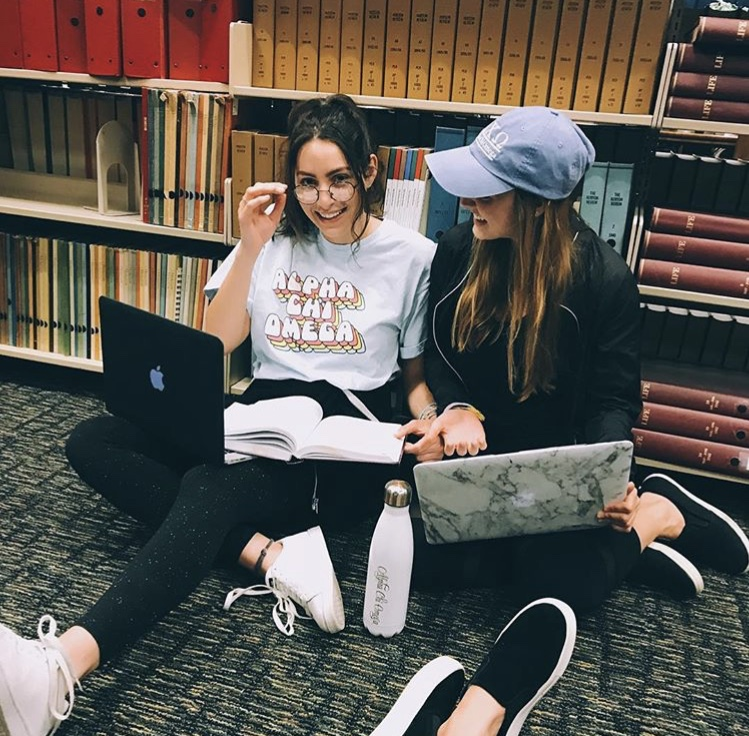 Two students sitting on the library floor with their laptops
