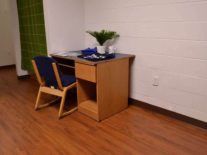 Osprey Landing wooden desk with cushioned chair and school supplies on the desk.