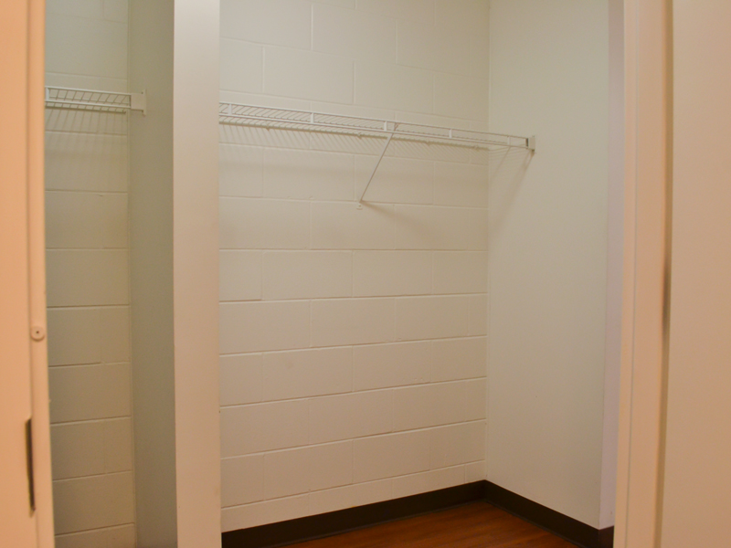 A white closet area with a clothing rack for clothes that doubles as a shelf.