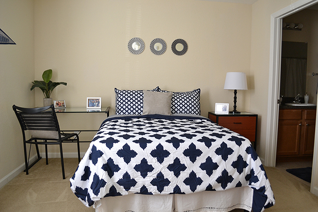 The Flats at UNF Bedroom with decor on the walls and a blue and white bedspread and neutral color night stand and table and chair.  The room is also connected to a private bathroom.