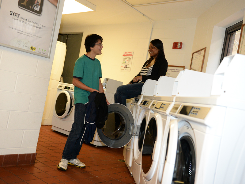Two students hanging out doing their laundry.