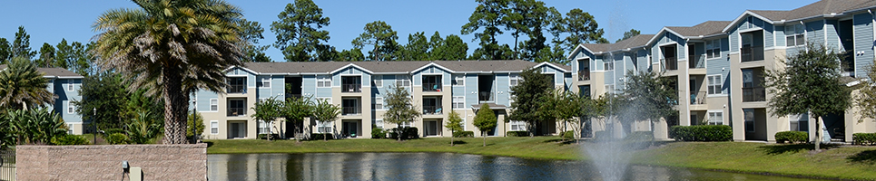 The Flats at UNF blue residence three story buildings with grass and a fountain lake out in front