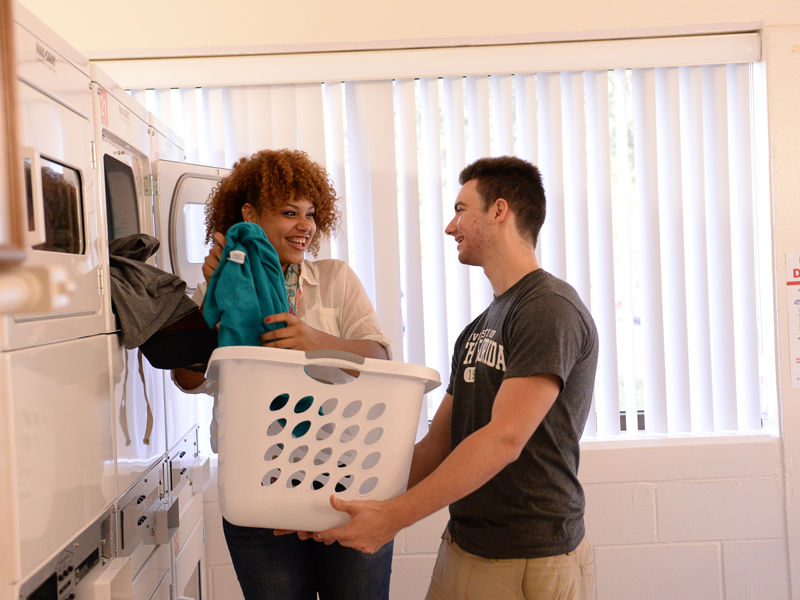 Two students in the Osprey Hall laundry room doing laundry while smiling and laughing.