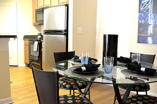 The Flats Kitchen Setup with a clear table and black chairs, a refrigerator, counter and stove