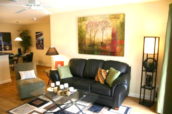 The Flats at UNF Living Room with black leather sofa and light colored chair with a painting on the wall and an area rug and several lamps throughout the room.