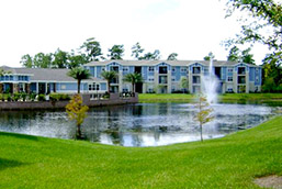 The Flats at UNF Outside with green grass, a lake with a fountain, trees and a light blue three-story building