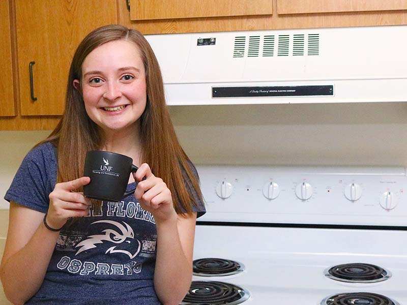 UNF resident drinking from a mug in her kitchen.