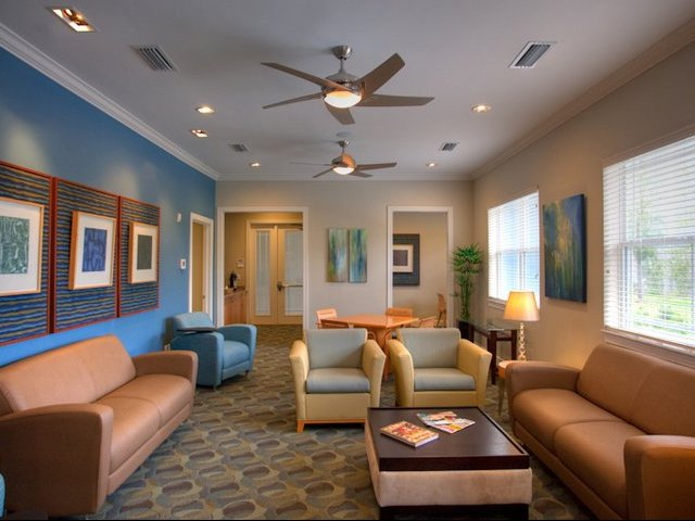 The Flats at UNF Lounge with blue and tan rugs and burnt tan colored furniture complete with a ceiling fan coffee table, picture frames on the walls.