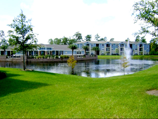 The Flats at UNF Outside area with green grass and blue buildings, a lake with fountain and a few trees.