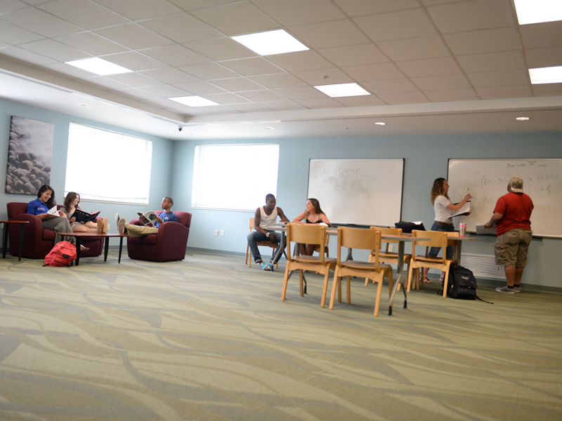 Residents talking and doing various activities in the Fountains resident area which has tables and chairs, windows, white boards, cushioned chairs and light blue walls.