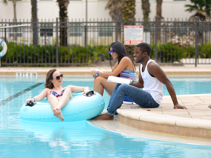 Three residents talking by the Fountains pool while one resident is on a float in a pool with The Fountains Residence in the bakground.