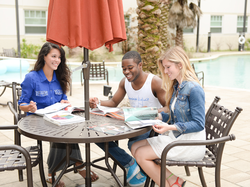 Three students sitting and studying at a table with an umbrella outside next to the Fountains pool.