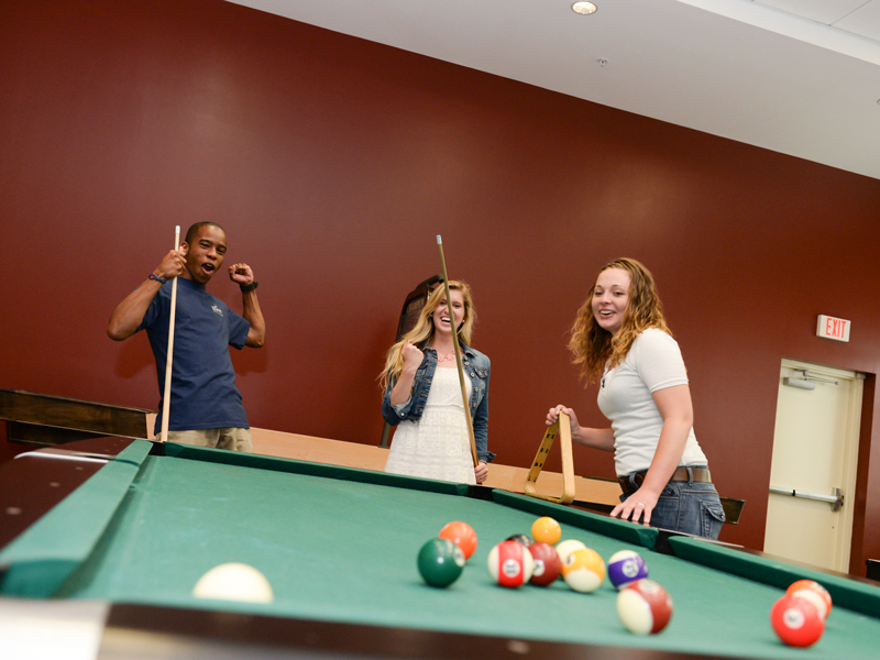 A few residents talking, laughing and playing pool in the Osprey Fountains pool room.