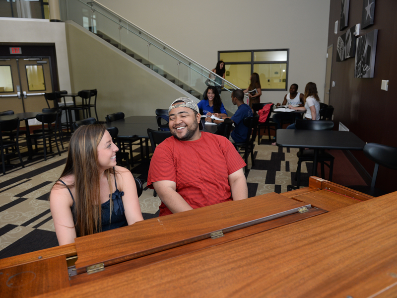 Two residents laughing while playing a rich wooded piano in a room with other students sitting at tables and others coming down the stairs.