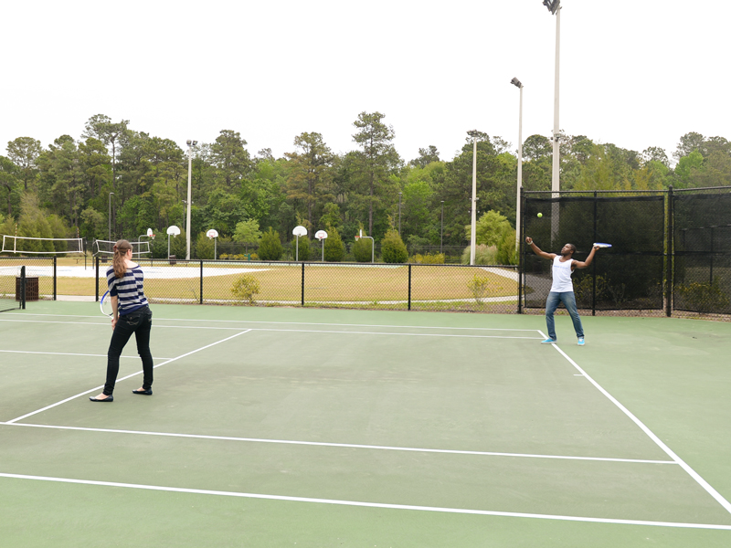 Two residents playing tennis on a tennis court.